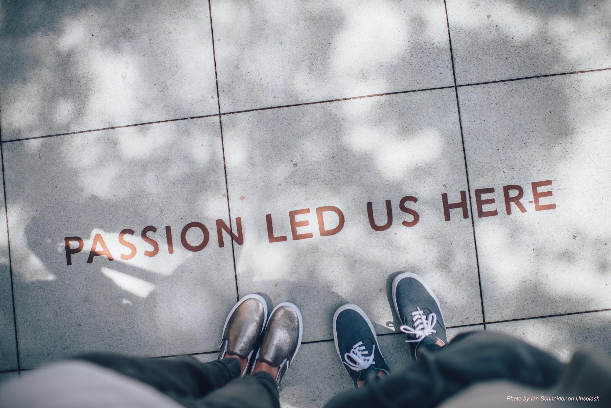 """Photo montrant les pieds de deux personnes sur un sol carrelé portant l'inscription """"Passion led us here""""."""